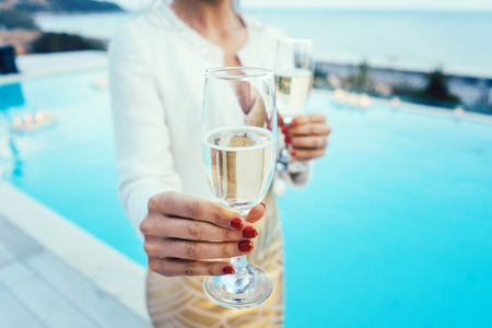 Woman handing glass of sparkling wine at pool and beach party wearing expensive dress