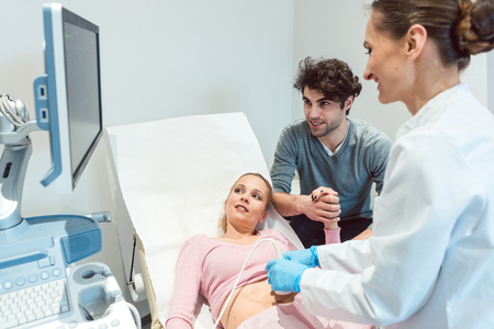 Couple in reproduction clinic being happy as the wife is pregnant as revealed by ultrasonic examination Banco de Imagens