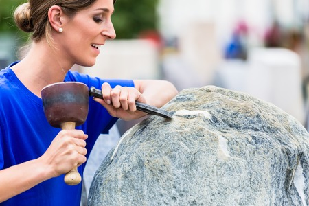 Stonemason working on boulder with sledgehammer and iron in workshop Stock Photo