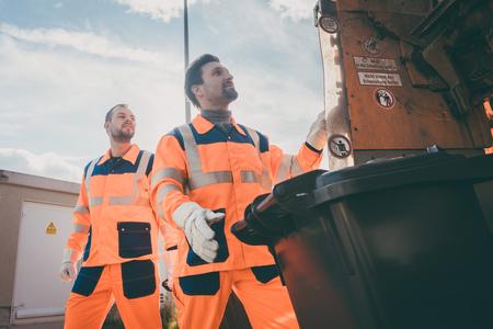 ゴミの取り除きのためにゴミ箱を空にすることに一緒に働く2人のゴミ屋 写真素材 - 103509475