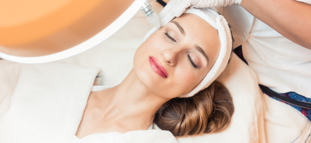Close-up of the face of a woman relaxing in a modern beauty center during facial treatment with innovative technology for softening wrinkles and rejuvenation