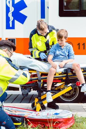 Emergency doctors caring for accident victim boy sitting on stretcher Archivio Fotografico