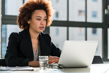 Portrait of African American woman sitting at desk while working on laptop in the office