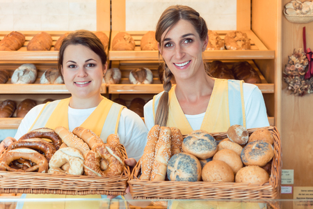 Two salesladies in bakery with basket of bread showing them to the camera