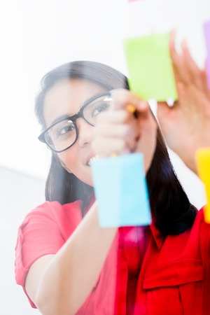 Portrait of young Asian employee looking at multiple reminders while planning her work in the office Stock Photo