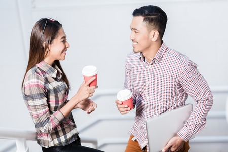 Happy young man and woman talking while drinking coffee from disposable cups during break at work
