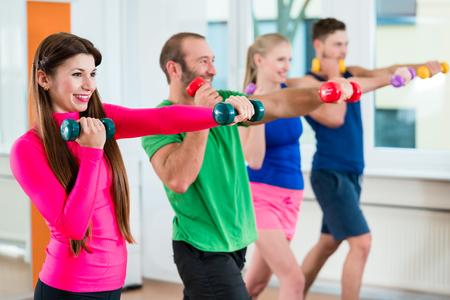 Uomini e donne che fanno allenamento con piccoli pesi in palestra studio fitness
