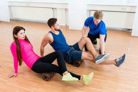 Man and woman with physiotherapist at gym doing floor gymnastics with roll Standard-Bild - 103620378