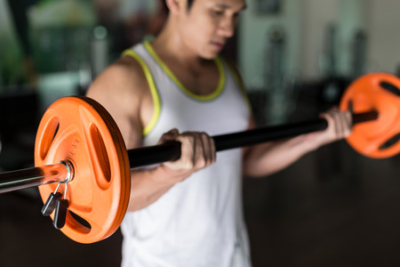 Determined young man holding a barbell with supinated grip while exercising bicep curls from standing position at the gym Stock Photo
