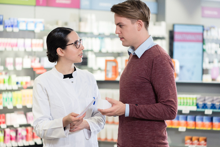 Handsome young man reading the prescription of an important medicine next to a helpful female pharmacist in a contemporary drugstore
