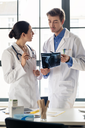 Two young dedicated doctors analyzing together the radiograph of the leg of a patient in a modern hospital Stock Photo