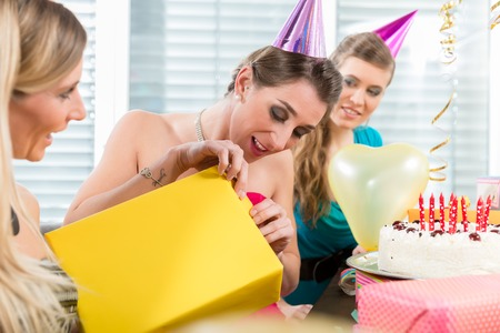 Portrait of a beautiful woman opening a surprise gift box wrapped in yellow paper while celebrating her birthday with her best friends at home Stock Photo