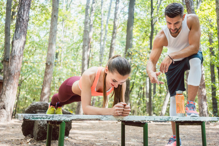Beautiful woman doing a plank with man watching and cheering Stock Photo