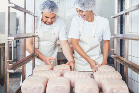 Butcher man and woman preparing meat for further processing putting in on a rack
