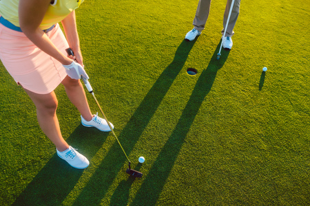 High-angle cropped view of a professional woman player holding the putter golf club, ready to hit the ball into the hole at the end of a difficult game with her partner or instructor Stock Photo