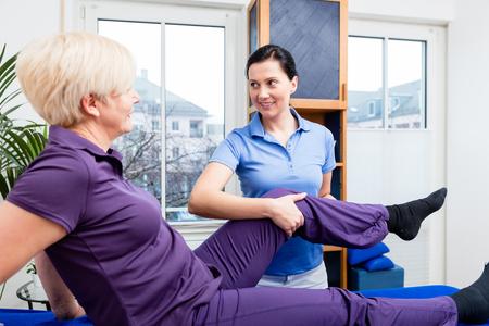 Terapeuta comprobando la articulación de la rodilla de la mujer mayor