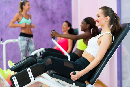 Side view of a beautiful woman smiling while exercising at the hip abductor machine during group workout at an exclusive fitness club for women
