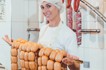 Butcher woman showing sausages on a rail with price Stockfoto