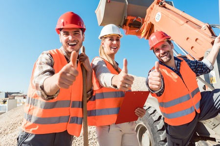Construction workers and civil engineer showing thumbs up to viewer