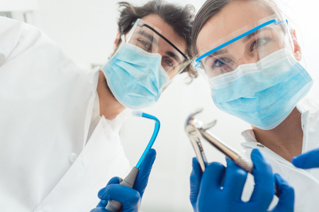 Funny dentists with their tools from point of view being a bit dangerous Stock Photo