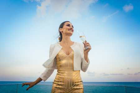 Woman sitting by the sea at a party on beach with glass of Champagne