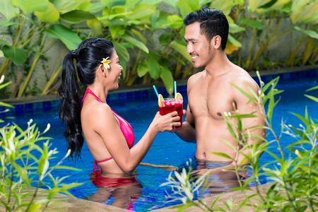Happy couple having drinks in pool in Asia