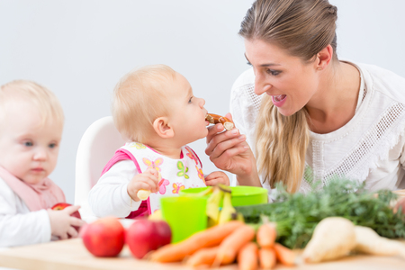 Portrait of a cute and healthy baby girl looking with curiosity at the pink fruit puree, while sitting on a high chair during meal with her happy mother at home