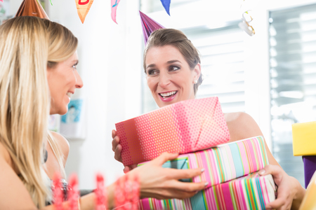 Happy adult woman having fun with party horns while celebrating her birthday with her best friend indoors in a decorated room