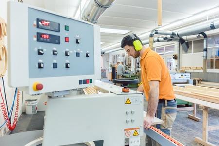Timmerman werkt in meubelfabriek op computergestuurde machine Stockfoto