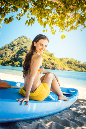 Beautiful woman sitting on boat close to the ocean beach looking at the water