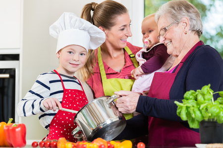 Mom, dad, granny and grandson together in kitchen preparing healthy food Stock Photo