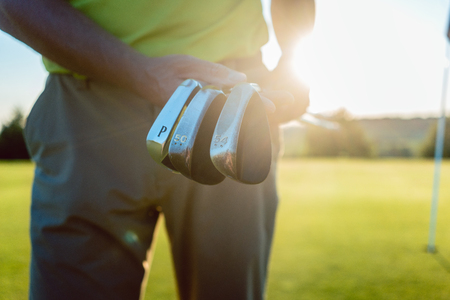 Close-up of the hands of a male professional player holding three different golf clubs, while standing against sunshine on the golf course of a modern country club 版權商用圖片