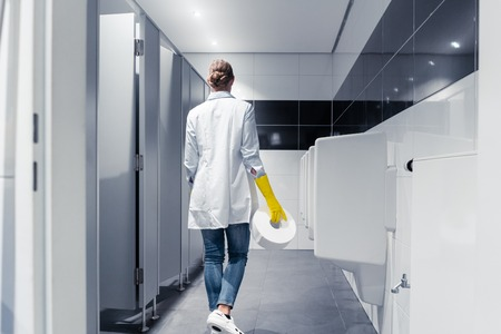Janitor woman changing paper in public toilet or restroom Standard-Bild
