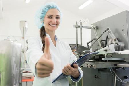 Retrato de una mujer feliz especialista en fabricación que muestra los pulgares hacia arriba como un signo de retroalimentación positiva después del control de calidad en una fábrica moderna