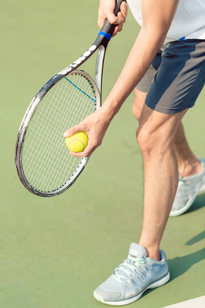 Low section of a professional player wearing gray sport shoes while holding the ball and the tennis racket during match on green surface Stock Photo