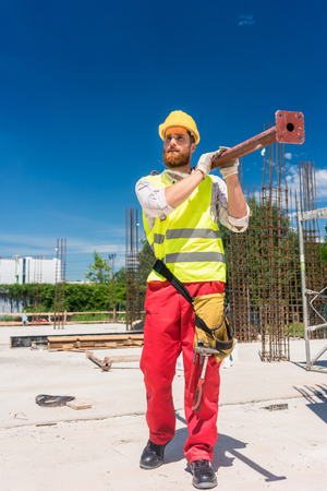 Full length of a blue-collar worker wearing safety equipment, while carrying a heavy metallic bar during work on the construction site of a residential building
