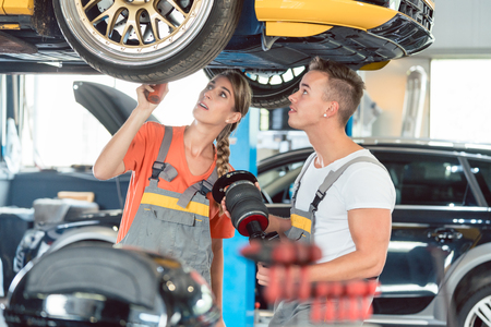 Experienced female auto mechanic checking tires before installing together with her colleague a new air suspension system in a modern automobile repair shop