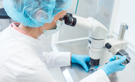 Doctor or scientist working on biotech experiment in laboratory on microscope