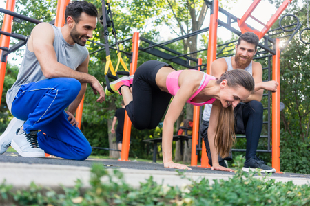 Low-angle view of a fit young woman doing leg extension exercise with suspension trainer, motivated by her cheerful athletic friends in a modern calisthenics park