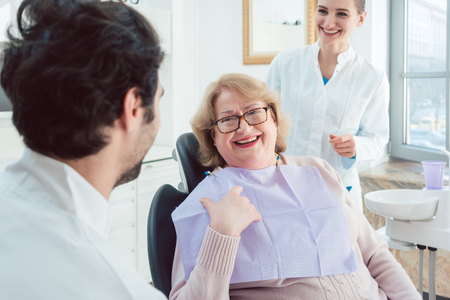 Dentist and assistant greeting senior patient in their surgery Stock Photo - 104968748
