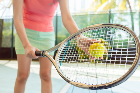 Close-up of the high-quality tennis racket of a professional female player serving at the beginning of a challenging match Stock Photo