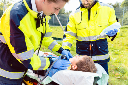 Paramedics measuring blood pressure of injured boy in front of ambulance