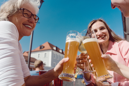 Three women drinking wheat beer on sunny day outdoors