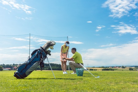 Full length of an experienced male instructor teaching a young woman the correct grip of the golf club on a green field in summer Stockfoto
