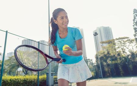 Vue latérale d'une joueuse professionnelle souriant tout en tenant la raquette et la balle avant de servir pendant un match de tennis Banque d'images