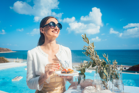 Woman enjoying some good food on beach house party with the sea and a pool 免版税图像