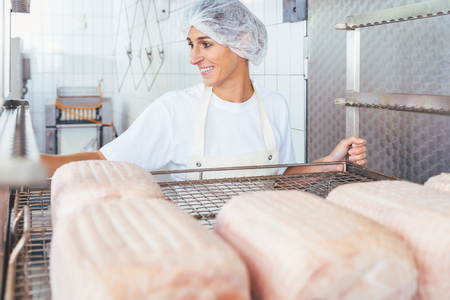 Woman in butchery processing meat ready to be smoked