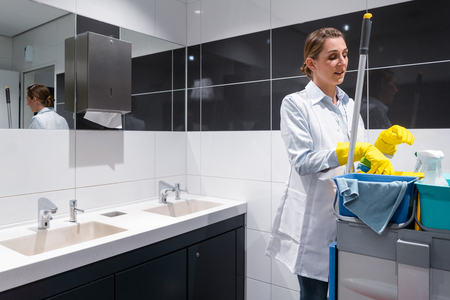 Janitor woman or charlady with her work tools looking at camera in toilet Standard-Bild