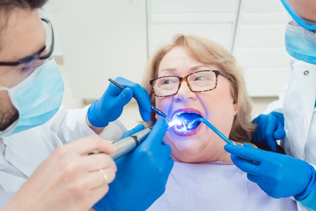 Dentists hardening toot crown with UV light treating senior patient Stock Photo