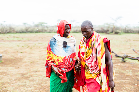 Two Massai men walking together in the rain Standard-Bild - 105353820